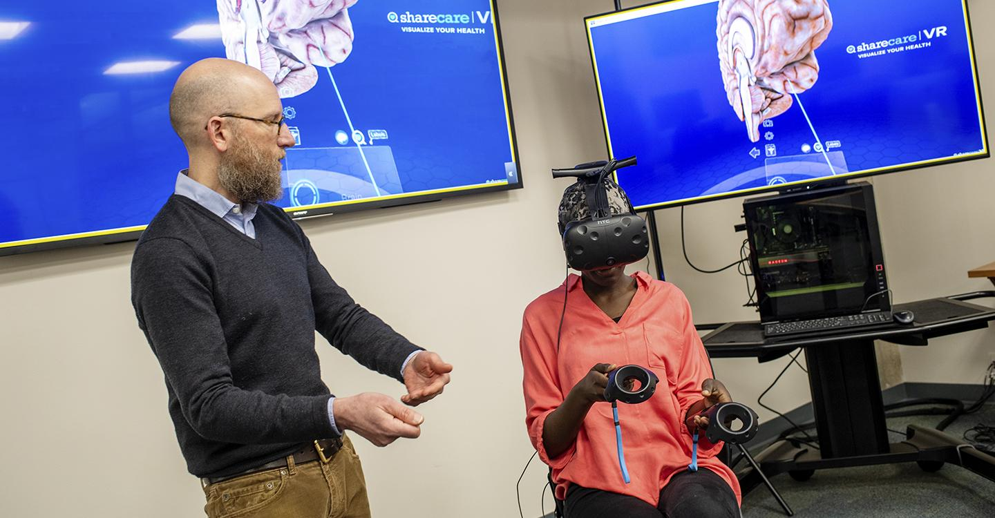 Eric Williams-Bergen, director of research and digital scholarship at St. Lawrence, works with a student using virtual-reality learning tools.